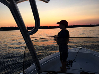 boy fishing on the bow of a boat at sunset
